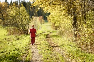 senior woman walking in sunny yellow autumnly nature